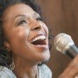 Close up of African American woman singing with microphone — Stock Photo