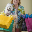 Senior woman holding shopping bags and dog — Stock Photo