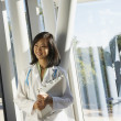 Young female Asian doctor standing next to window  — Stock Photo