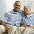 Portrait of African father and son on sofa — Stock Photo #13231594