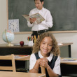 School girl smiling for the camera from her desk - Stock Photo