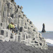 Couple sitting on rock ledge at beach — ストック写真
