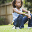 African girl sitting on soccer ball - Foto Stock