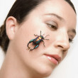 Young woman holding a beetle on her cheek — Stok fotoğraf