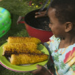 Young boy carrying grilled corn - Stock Photo