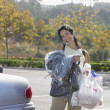 Woman carrying dry cleaning and bags of groceries to her car — Stock Photo
