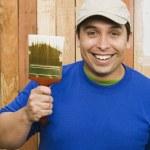 Hispanic man painting fence — Stock Photo #13231669