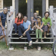 Group of friends on porch of cabin — Stock Photo