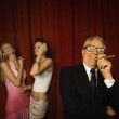 Young women preening themselves while older man smokes a cigar — Stock Photo