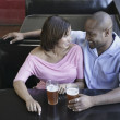 Stock Photo: High angle view of a young couple sitting at a restaurant table with glasses of beer