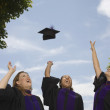 Graduates throwing mortar boards into air - Stock Photo