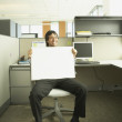Hispanic businessman holding a blank dry erase board in his lap — Stock Photo