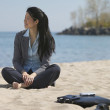 Asian businesswoman sitting at beach with bare feet — Stock Photo