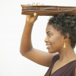 Profile of woman holding bundle of twigs on head — Stock Photo