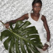Portrait of African woman holding Monstera leaf - Stockfoto