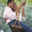 Stock Photo: Young Asicouple on swing