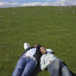 Couple laying in grass together — Stock Photo