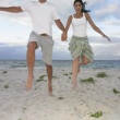 Couple jumping on the beach — Stock Photo #13231879