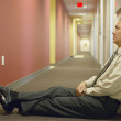 Businessman sitting on floor of hallway — Stock Photo