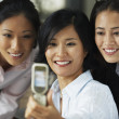 Royalty-Free Stock Photo: Asian businesswomen taking own photograph with cell phone