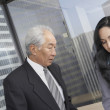 Senior Asian businessman and businesswoman in front of window  — Stock Photo