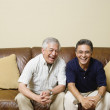 Portrait of elderly men sitting on couch laughing — Stock Photo