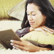 Woman reading book on bed - Stockfoto