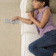 Stock Photo: Young Asian girl watching television on sofa