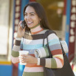 Hispanic woman on cell phone outdoors — Stock Photo
