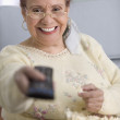 Elderly woman watching television — Stock Photo