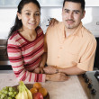 Stock Photo: Young couple in kitchen looking at camera