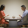 Asian couple kneeling having tea — Stock Photo #13231986