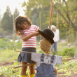 Young Hispanic girl putting hat on scarecrow — Stockfoto