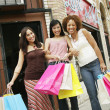 Low angle view of three young women holding shopping bags on the sidewalk — Stock Photo