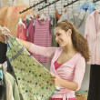 Young woman shopping for blouse - Stock Photo