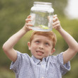 Young boy looking at frog in glass jar outdoors - Stock Photo