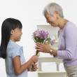 Asian girl giving grandmother bouquet of flowers — Stock Photo