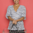 Portrait of woman holding grocery basket - Stock Photo