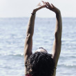 Stock Photo: Woman stretching at ocean