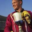 Male goalie triumphantly holding trophy — Stock Photo