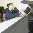 Businesswomdropping computer monitor over balcony — Stock Photo #13232120