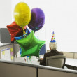 Businessman in a cubicle with a party hat on and a bunch of balloons — Stock Photo