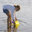 Portrait of girl scooping up water in bucket at beach - Stock Photo