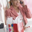 Woman in store on cell phone - Stock Photo