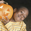 Young boy smiling for the camera with a jack o lantern - Stock Photo