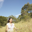 Wommeditating in field — Stock Photo #13232165