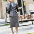 Businesswoman outdoors using mobile phone - Stock Photo