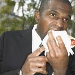 Businessman eating hotdog — Stock Photo