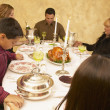 Hispanic family saying grace at dinner table - Stock Photo