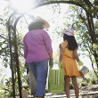 Mother and daughter carrying gardening supplies outdoors - Stock Photo
